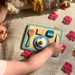 child playing with breakfast set